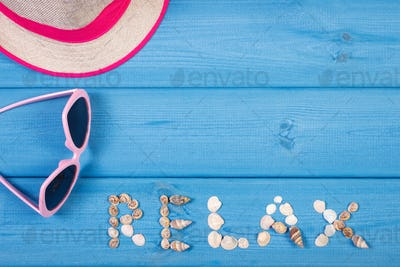 Word relax made of seashells, sunglasses and straw hat on boards, concept of summer time