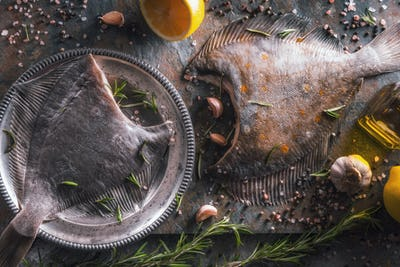 Two raw flounders with different seasoning on the stone background top view