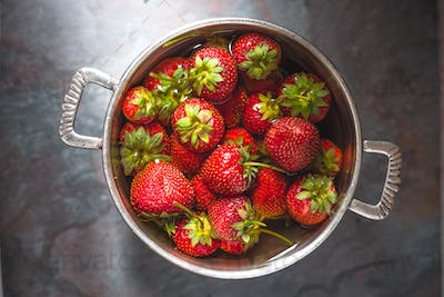 Strawberries in a tin bowl in the center of the table