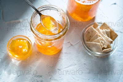 Jam from pineapple in jars on a white background and cookies