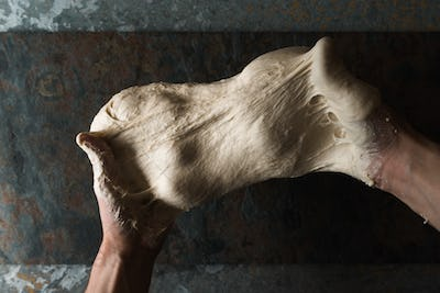 Dough for bread in the hands top view