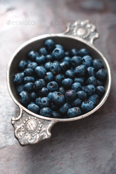 Berry bilberry in a tin bowl on a gray slate