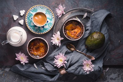 Still life with creme brulee , avocado and cup of coffee on the stone background top view