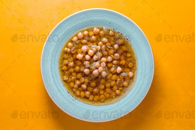 Greek chickpea soup in the white plate on the yellow background  top view