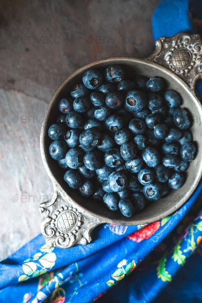 Tin bowl with blueberries, colored napkin on slate copy space