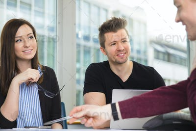 Smiling Business People Looking At Colleague Explaining At Desk