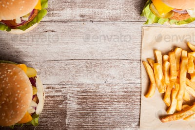 Cheeseburgers and french fries on wooden plate