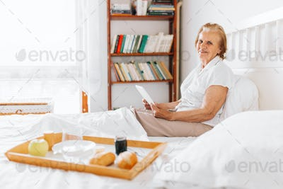 Elderly woman having breakfast in bed whilst using her tablet