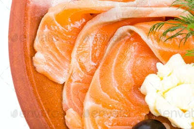 Sliced salmon and butter on plate.