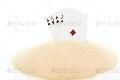 Playing cards on heap of sand.