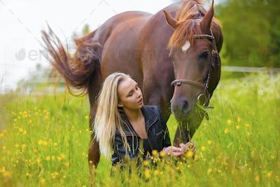Beautiful woman feeding her arabian horse with snacks in the field