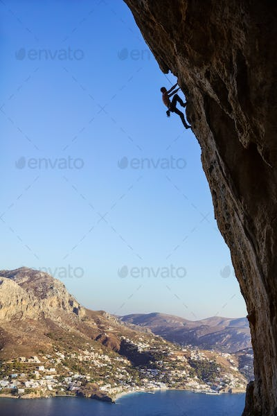 Young man climbing overhanging cliff against beautiful view of coast