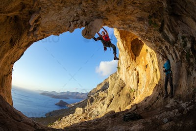 Young man lead climbing on ceiling in cave