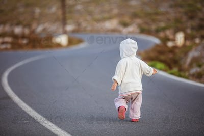 Little girl running down road in countryside