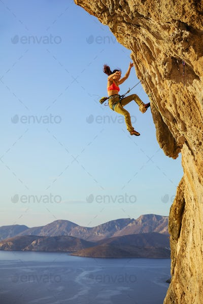 Female rock climber falling off cliff while lead climbing