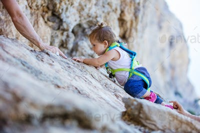 Little girl climbing up cliff