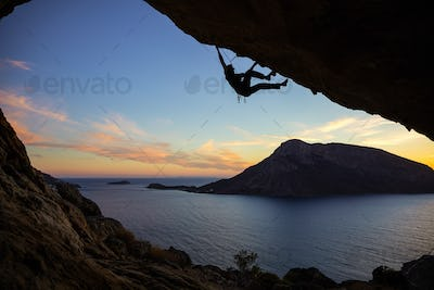 Young man climbing along ceiling of cave at sunset