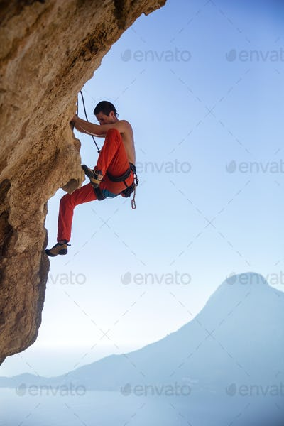 Young man climbing on overhanging cliff