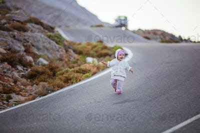 Happy little girl running down road