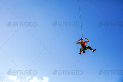 Rock climber swinging on rope and flexing muscles