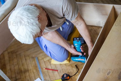Mature man using electric screwdriver while making bookcase