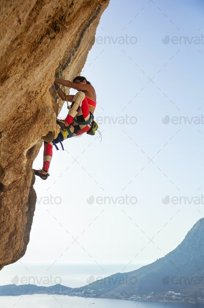 Young woman struggling to climb challenging route
