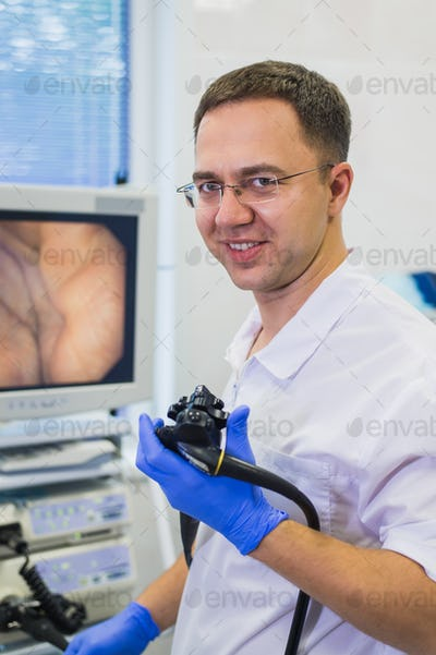 proctologist doctor holding Ligador hemorroidal in office