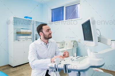 Male doctor with ultrasonic equipment during ultrasound medical examination