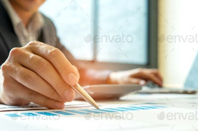Businessmen analyzing graphs and Left hand is using laptop,The r