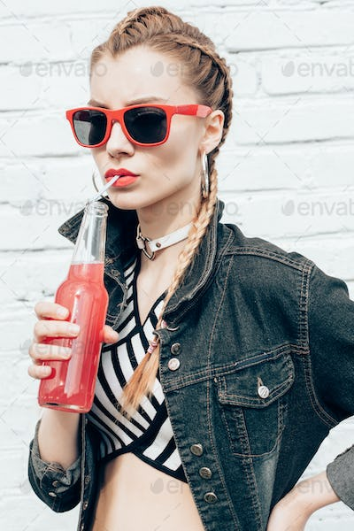 Young woman drinking colorful cocktails from bottles