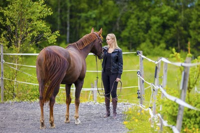 Young woman with her arabian horse standing at a riding course