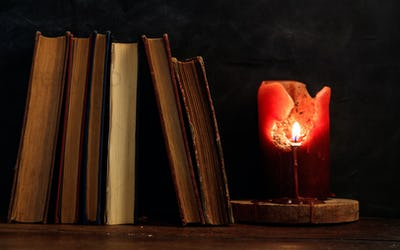 Vintage books and candle on dark background