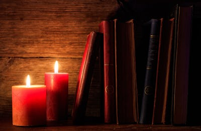 Vintage books and candles on dark background