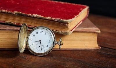 Vintage books and pocket watch on dark background