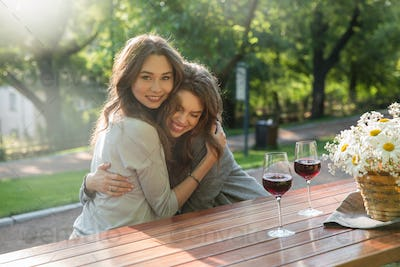 Cheerful young two women sitting outdoors in park drinking wine