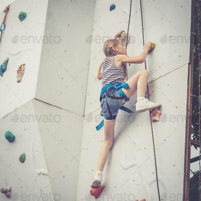 little girl climbing a rock wall outdoor.