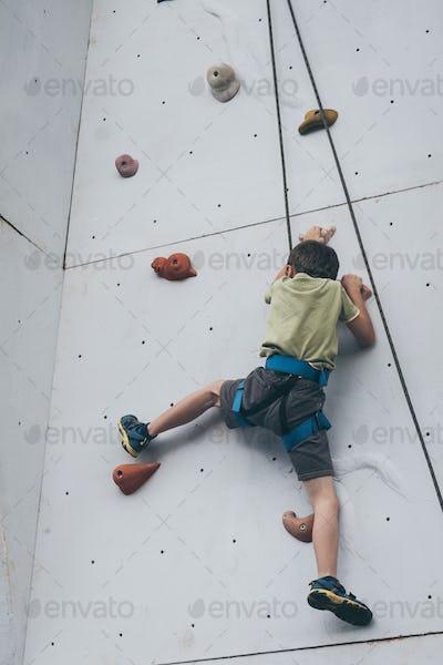 little boy climbing a rock wall outdoor.