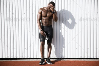 Young afro american male athlete holding water bottle