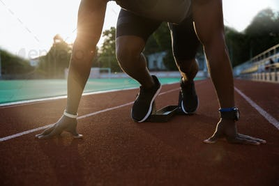 Cropped image of a young african male sprinter getting ready