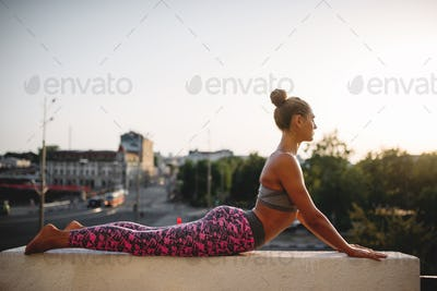 Woman doing yoga exercise, city on background