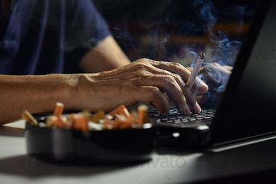 Man holding lit and smoking cigarette between fingers and working on a laptop computer