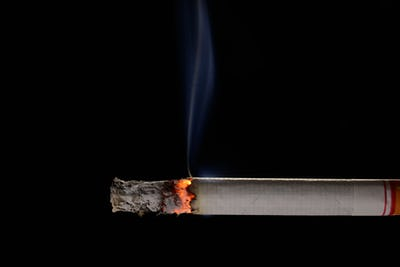Lit and burning cigarette with smoke on black background