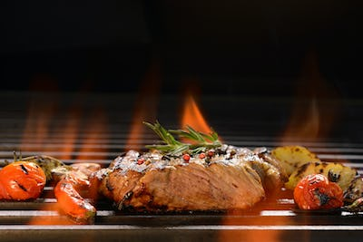 Grilled pork steak with vegetable on the flaming grill