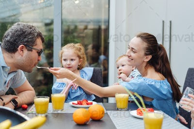 Happy family eating fresh fruit breakfast