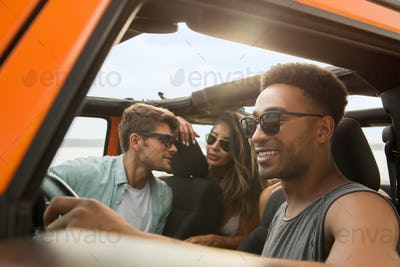 Group of multiethnic friends sitting in a car