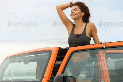Happy smiling woman leaning on a car