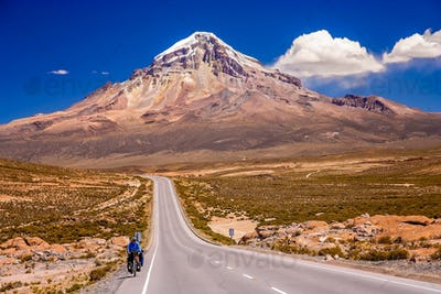 Cycling on the beautiful road in front of Nevado Sajama volcano