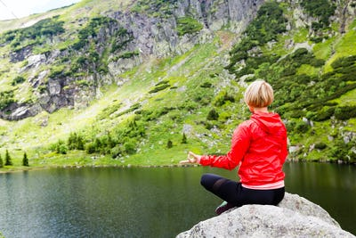 Woman meditating in yoga pose in front of mountain lake
