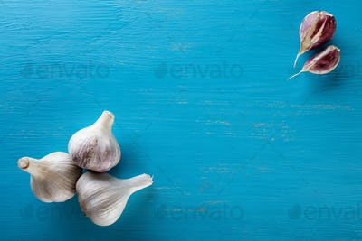 Three heads and cloves of garlic on a wooden table