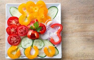Fresh sliced vegetable salad on a white plate